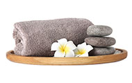 Wooden tray with towel, spa stones and flowers